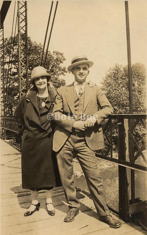 Couple standing on a bridge.