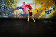 A Mexico City resident walks in the rain near the Bellas Artes Station.