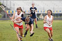 A West Springfield lacrosse player is tripped up while battling for the ball against a couple of Annandale players.