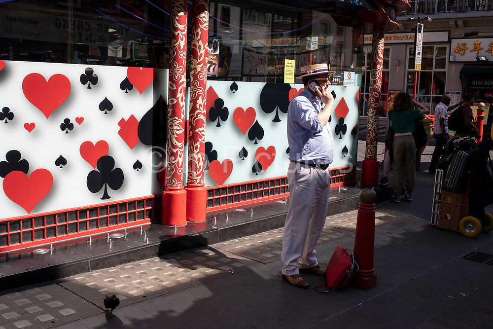 Street scene with a man wearing a straw boater hat outside a gaming shop in Chinatown in Soho, London, United Kingdom. The present Chinatown is in the Soho area occupying the area in and around Gerrard Street. It contains a number of Chinese restaurants, bakeries, supermarkets, souvenir shops, and other Chinese-run businesses and is in itself a major tourist destination.