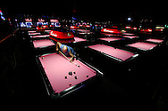 James Harris plays pool at the Pink Galleon in south St. Louis County. The bar features a couple dozen pink-topped pool tables.