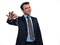one caucasian realtor man real estate agent businessman teasing holding offering keys isolated studio on white background