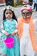 Two young Mexican girls wearing skeleton face paint during the Dead of the Dead festival in San Miguel de Allende, Mexico. The multi-day festival is to remember friends and family members who have died using calaveras, aztec marigolds, alfeniques, papel picado and the favorite foods and beverages of the departed.