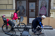 Younger generations of a Polish mother and child pass a bent, elderly and disabled lady in a Krakow suburb, on 24th September 2019, in Krakow, Malopolska, Poland.