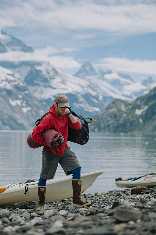A sea kayak guide unloads gear at Topeka Beach in Johns Hopkins Inlet in Alaska's Glacier Bay National Park and Preserve. Photo © Robert Zaleski / rzcreative.com<br /> —<br /> To license this image contact: robert@rzcreative.com