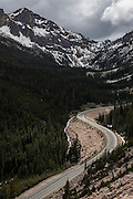 A car drives Highway 20 below Washington Pass, North Cascades Scenic Highway Corridor, Washington.
