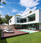 Exterior modern white villa with pool and garden, nobody inside