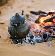 Teapot sat on fire embers at a Tuareg camp, Sahara Desert, Libya