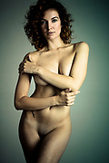 Front view of beautiful sexy nude woman against a gray background looking directly at camera with arms across chest. Toned photograph