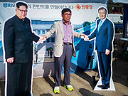 "15 JUNE 2018 - SEOUL, SOUTH KOREA: A man stands between cardboard cutouts of North Korean leader Kim Jong-un (left) and South Korean President Moon Jae-in during a rally to mark the anniversary of the signing of the June 15th North–South Joint Declaration between South Korea and North Korea. The Declaration was negotiated by late South Korean President Kim Dae-jung and North Korean leader Kim Jong-il and signed on 15 June 2000. It was a part of South Korea's ""Sunshine Policy,"" which guides the South's relationship with North Korea. This year's observance of the anniversary was bolstered by the recent thawing in relations between North Korea and South Korea and the US.     PHOTO BY JACK KURTZ"