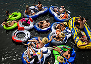 A group of at least 15 people float on connected inflatables down the American River in the Sunrise Recreational Area near Rancho Cordova, Calif., during Memorial Day weekend on Sunday, May 24, 2020. Masks were hard to find on the shoreline, and few seemed to heed social distancing measures. State health officials on Thursday reversed Sacramento County's plans to allow groups of up to 10 get together, with social distancing, starting this weekend.