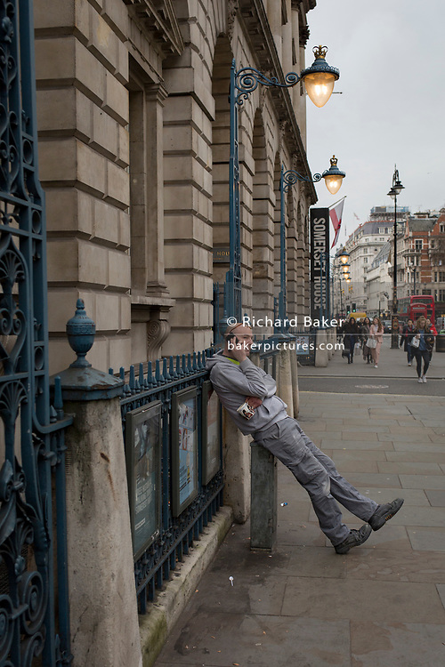 A man leans against the railings of Somerset House on the Strand, to make a mobile phone call, 18th February 2019, in London, England.