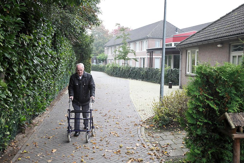 elderly man walking with a walker