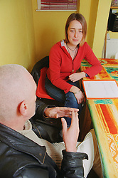 Assistant manager discussing resettlement plan with resident of homeless hostel for people with learning difficulties,