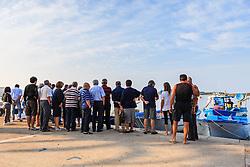 Porto Cesareo (Lecce). Ogni mattina, tempo, mare e legislazione permettendo, sul lungomare della riviera di Ponente, proprio di fronte all'Isola dei Conigli, i pescatori del posto, dopo una notte in mare con le loro barche e pescherecci di legno, danno vita al caratteristico mercato del pesce fresco. © Massimiliano Manno