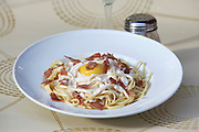 plate of linguine with bacon and fried egg