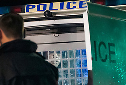 © Licensed to London News Pictures. 08/02/2019. Cheam, UK. A man looks out from inside a police van after being detained by armed officers outside Cheam Leisure Centre. The leisure centre is 680 metres from where a woman in her 30's was stabbed to death at 3pm on Friday. Two men have been arrested. Photo credit: Peter Macdiarmid/LNP