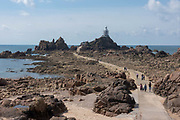 La Corbiere Lighthouse, undergoing renovations, on 2nd September 2017 in Jersey on the Channel Islands, United Kingdom. La Corbière lighthouse is situated on a tidal island at the extreme south-westerly point of Jersey in St. Brelade. The name means a place where crows gather, deriving from the word corbîn meaning crow. Although seagulls are more common nowadays. Accessible at low tide.