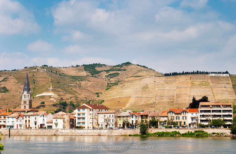 The town Tain l'Hermitage, the riverside side, the river Rhone.  The name of the town painted in large white letters   The Hermitage vineyards on the hill behind the city Tain-l'Hermitage, on the steep sloping hill, stone terraced. Sometimes spelled Ermitage.  Tain l'Hermitage, Drome, Drôme, France, Europe