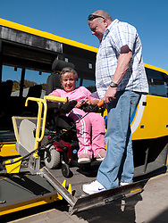 Wheelchair used and helper using lift to get off coach