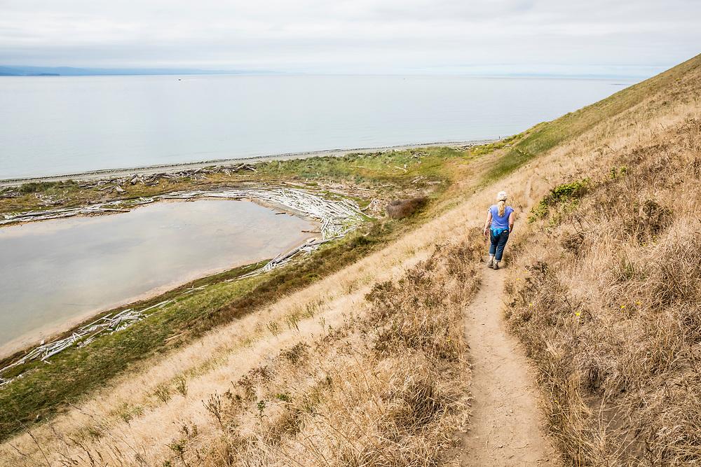 A woman walking on Ebey's Landing Bluff Trail, Whidbey Island, Washington, USA.