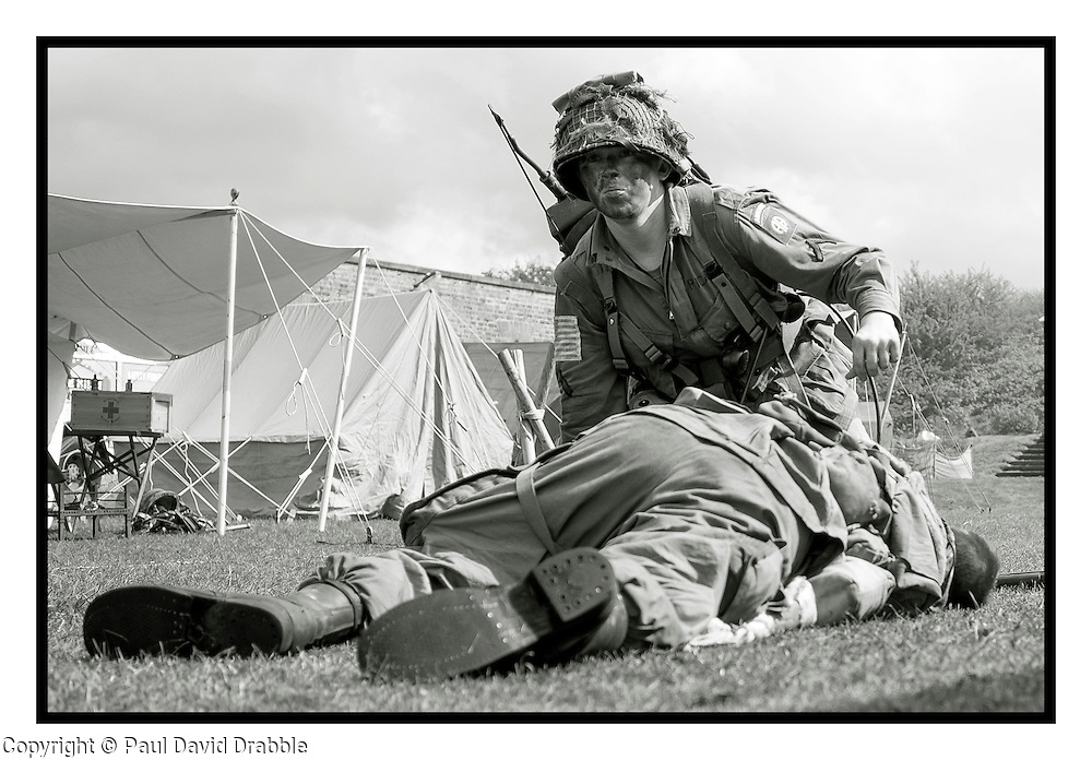 """Members of the US 82nd Airborne/505th RCT living History Group take part in the first days battle re-enactment at Fort Paull. A reenactor checks on a """"casualty"""" as the Americans are pushed back <br /> <br />   03 May 2015<br />   Image © Paul David Drabble <br />   www.pauldaviddrabble.co.uk"""
