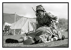 "Members of the US 82nd Airborne/505th RCT living History Group take part in the first days battle re-enactment at Fort Paull. A reenactor checks on a ""casualty"" as the Americans are pushed back <br /> <br />   03 May 2015<br />   Image © Paul David Drabble <br />   www.pauldaviddrabble.co.uk"