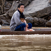 Man sheltering young son in small boat on Mekong River (, Laos - Nov. 2008) (Image ID: 081127-0801273a)