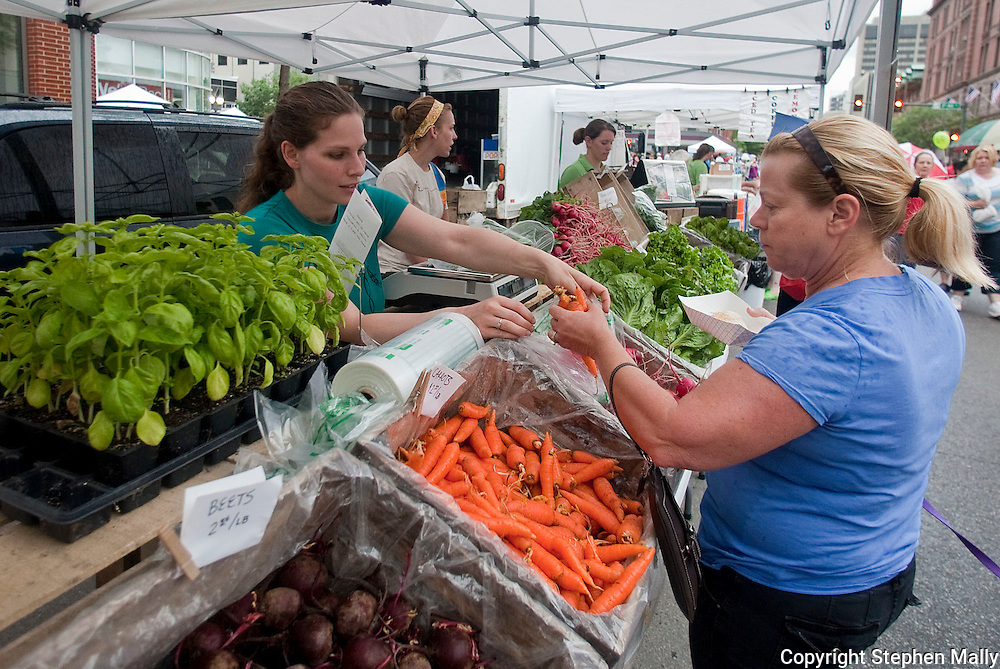 Jen Digmann (from left) of Marion holds open a bag for Jackie Oster of Cedar Rapids as she picks out organic carrots at the Grinnell Heritage Farm booth at the Downtown Farmers' Market in Cedar Rapids on Saturday, June 5, 2010.