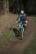 Model released image of teenage boy cycling in the countryside in winter, Suffolk, England, UK