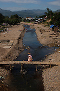 A budist nun crossing a wood bridge in Hsipaw, Myanmar.<br />