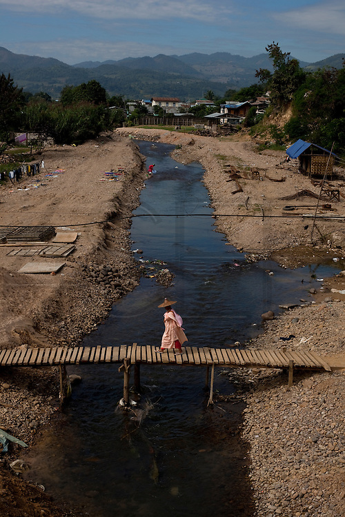 A budist nun crossing a wood bridge in Hsipaw, Myanmar.<br /> Note: These images are not distributed or sold in Portugal