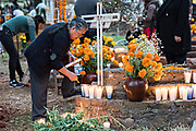 An elderly woman lights candles on the gravesite of a family member during the Day of the Dead festival October 31, 2017 in Tzintzuntzan, Michoacan, Mexico.