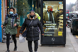 © Licensed to London News Pictures. 02/03/2021. London, UK. Women wearing protective face coverings walk past the government's 'Every covered face is making a difference' awareness poster in north London. The number of Covid-19 infection rate and deaths have dropped more than a quarter within a week as the effect of lockdown restrictions and vaccine rollout is making an impact. Six cases of the P1 variant have been identified in people who recently returned from Brazil. Photo credit: Dinendra Haria/LNP