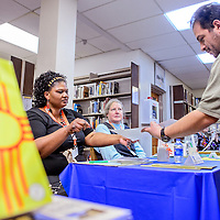 041214       Cable Hoover<br /> <br /> Authors Essie Yazzie, left, and Penny Durant autograph a poster for Markos Chavez during the 2014 Authors Festival at Octavia Fellin Public Library in Gallup Saturday. The even featured 22 authors from New Mexico and Arizona.