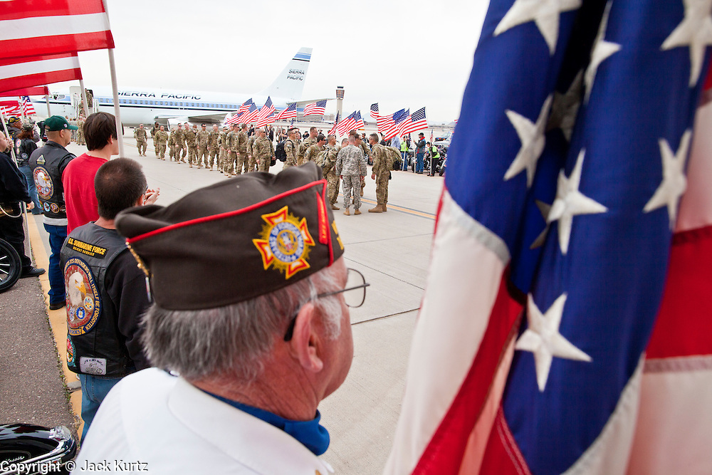 """15 JANUARY 2012 - PHOENIX, AZ:    A member of the VFW stands with a flag waiting as returing soldiers get in formation at the The 161st Air Refueling Wing of the Arizona Air National Guard in Phoenix. About 100 soldiers of A (Alpha) Company of the 422nd Expeditionary Signal Battalion (referred to as """"Alpha 4-2-2"""") of the Arizona Army National Guard returned to Arizona on Sunday, Jan. 15, following a nearly year-long deployment to Afghanistan. More than 10,000 Arizona Army and Air National Guard Soldiers and Airmen have been ordered to federal active duty in support of Operations Noble Eagle, Enduring Freedom, Iraqi Freedom, and New Dawn since September 2001. Approximately 200 Arizona National Guard Soldiers and Airmen are still serving on federal active duty overseas.  PHOTO BY JACK KURTZ"""