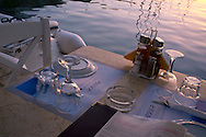 A taverna table on the waterfront in Lakka harbour at sunset.  Paxos, The Ionian Islands, The Greek Islands, Greece, Europe