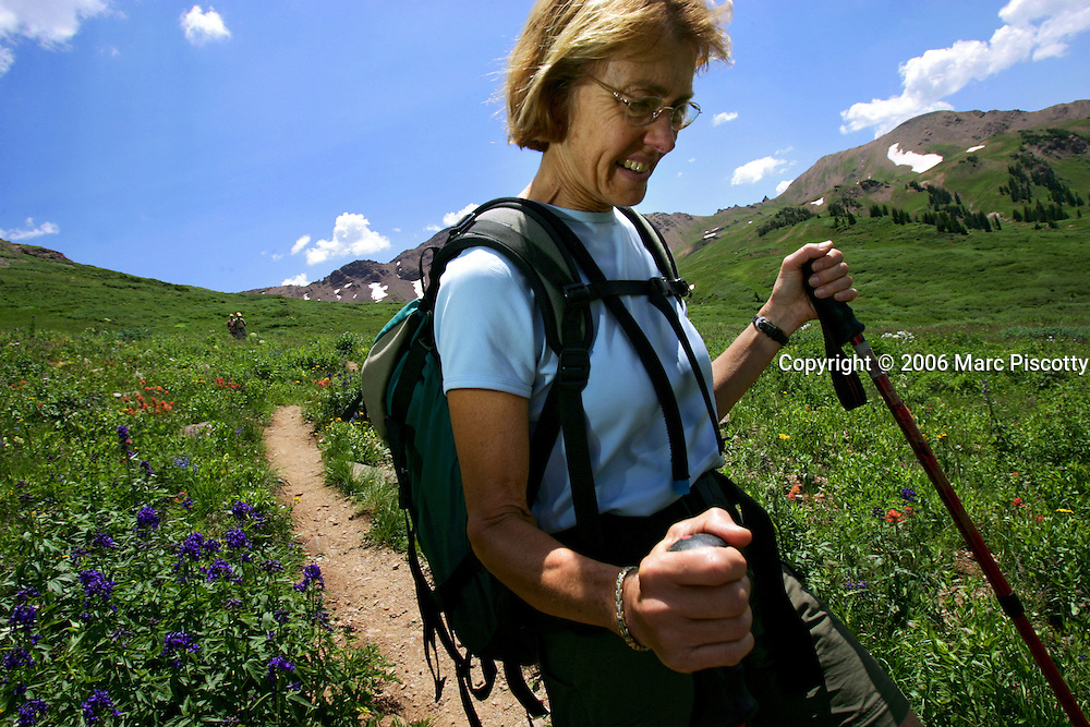 """Aspen, Co. and Crested Butte, Co. are hours apart by car and probably worlds apart in attitude but only separated by 24 miles on a map. Many hikers are starting to take one of a number of mountain passes on foot and stay the night in the other town and then hike, bike, drive or fly back the following day. Depending on the route chosen and the ability of the hiker, it takes about 5 to 9 hours to hike between the two towns. Most hikers choose the trails that converge on 12,490-foot West Maroon Pass ? the shortest of the available options at 10.5 miles. The trail offers a steady uphill from either side, with ample time to prepare for the last steep and loose rocky sections before the pass. Margaret Marshall of Conway, N.H. makes her way down West Maroon Pass trail on Sunday July 16, 2006 back to the trailhead on the Crested Butte side. It was Marshall's first time hiking the trail with her daughter and said the hike was """"abolutely gorgeous""""..(MARC PISCOTTY/ © 2006)"""
