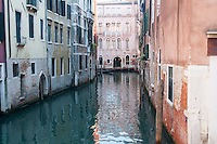 romantic view: water reflections in a venice channel in italy with incoming gondola