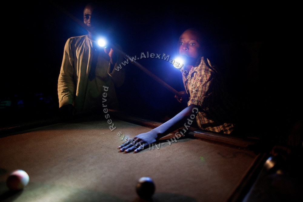 Boys are playing pool at night, on the roads in Bagega, pop. 9000, a large village affected by lead poisoning due to the unsafe techniques employed for extracting gold, in Zamfara State, Nigeria. It is mainly caused by ingestion and breathing of lead particles released in the steps to isolate the gold from other metals. This type of lead is soluble in stomach acid and children under-5 are most affected, as they tend to ingest more through their hands by touching the ground, and are developing symptoms often leading to death or serious disabilities.