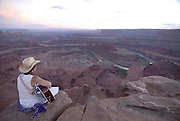 Young woman playing the guitar on the edge of Dead Horse Point state park, Utah