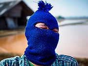 28 MARCH 2018 - BAN LAEM, PHETCHABURI, THAILAND: A worker puts on a face mask before going to work in a salt field during the 2018 salt harvest in Petchaburi province, about two hours south of Bangkok. Although daytime temperatures are over 90F, most workers wear face masks to protect themselves from the sun. Sea salt is made in provinces south of Bangkok by flooding fields with ocean water after the rainy season. As the fields dry out from evaporation, workers go into the fields and gather the salt left behind.        PHOTO BY JACK KURTZ
