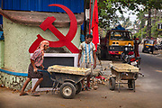 Workers in the street in front of the communist Hammer and Sickle on 28th February 2018 in Kochi, Kerala, India. Today the  largest parties in Kerala politics is the Communist Party of India Marxist.
