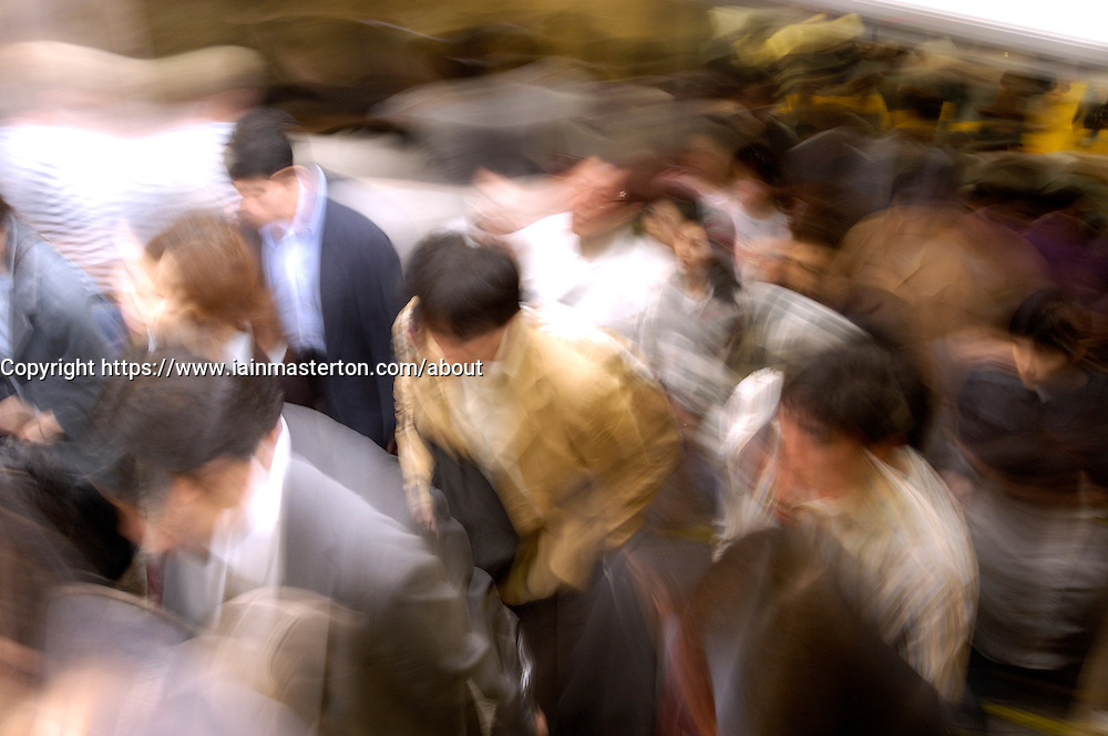 Crowds of commuters in a Tokyo railway station in Japan, with motion blur