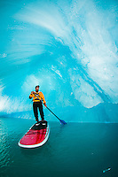 One man on stand up paddle board (SUP) maneuvers in an iceberg cavern on Bear Lake in Kenai Fjords National Park, Alaska.