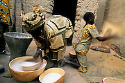 """(MODEL RELEASED IMAGE). After pounding rice into flour in a large wooden mortar, Pama Kondo sifts it to get rid of any remaining hulls. Behind her, 10-year-old Fatoumata (daughter of Fatoumata Toure, Pama's co-wife) does much the same with some sorghum. Can she foresee a day when she will no longer have to pound grain? """"That's what children are for,"""" she replies seriously. Hungry Planet: What the World Eats (p. 212). The Natomo family of Kouakourou, Mali, is one of the thirty families featured, with a weeks' worth of food, in the book Hungry Planet: What the World Eats."""