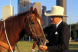 man standing with a horse in front of the downtown Houston skyline