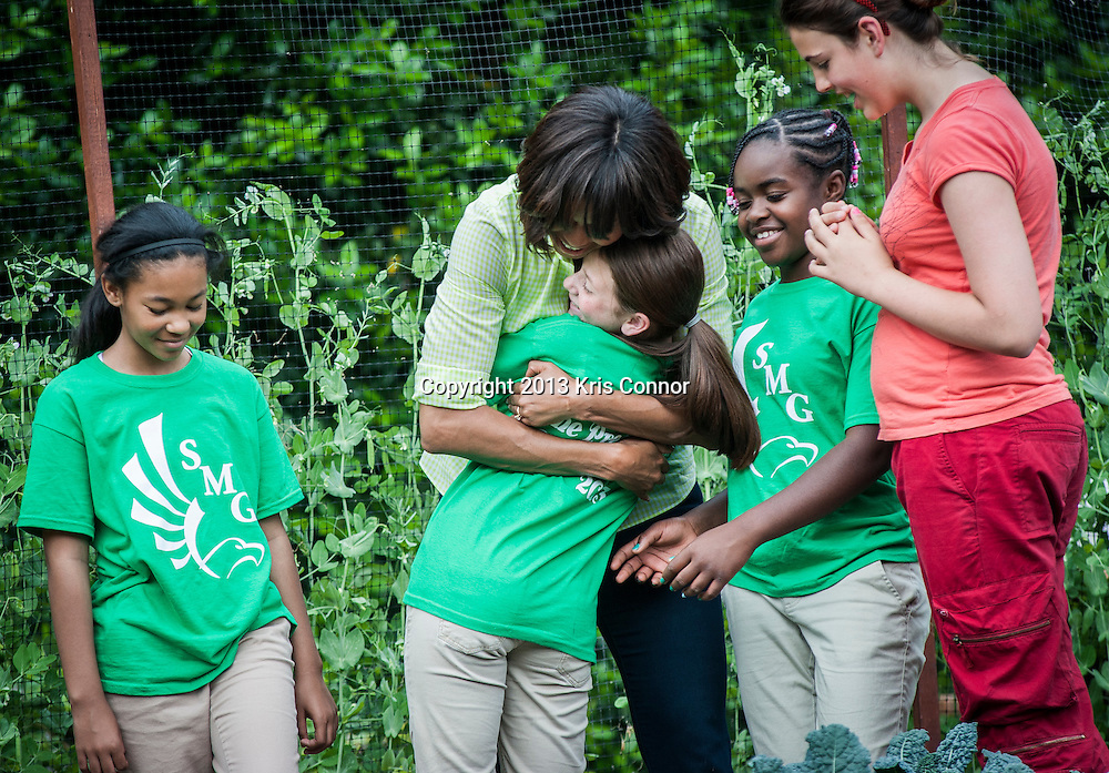 (L-R) Eliza Croom, Kyla Bourne, Rachel Bradley of Sarah Moore Greene Magnet Technology Academy School, Knox County, TN  hug the First Lady during an event where they  harvested the White House Kitchen Garden for the fifth year in a row at the White House on May 28, 2013 in Washington DC. Photo by Kris Connor