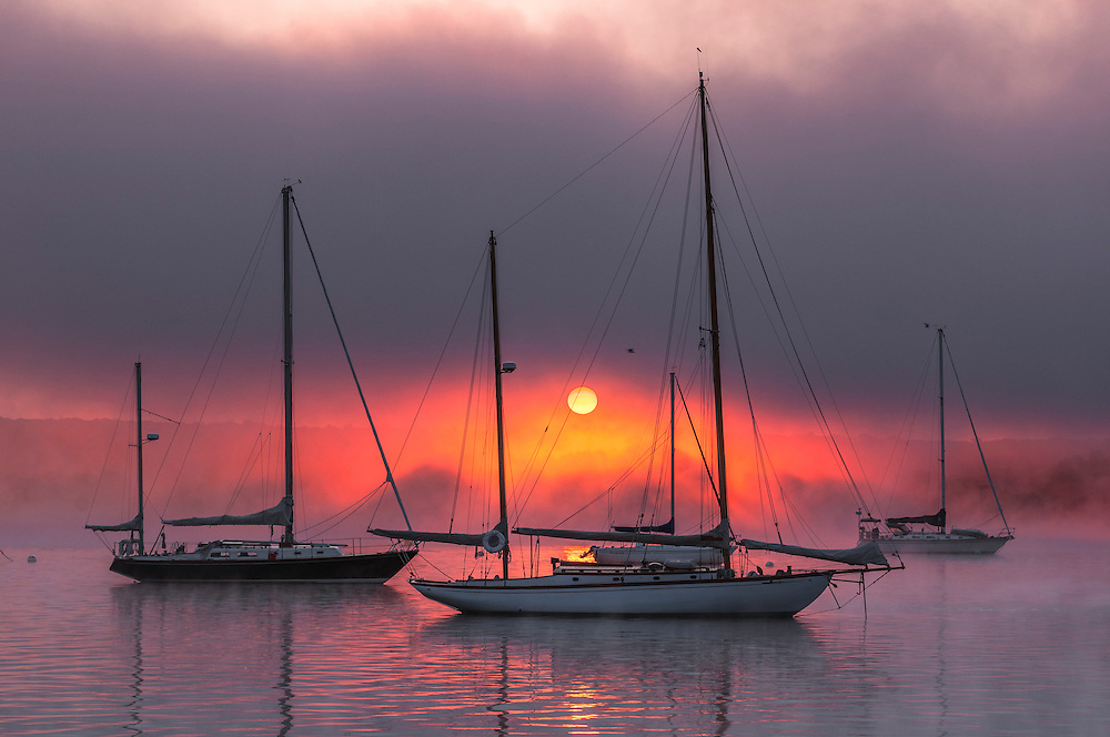 Sunrise filtered through thick fog and three sailboats moored in CT river, Essex, CT