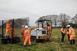 HS2 contractors erect security fencing in front of works to fell a row of hundred-year-old oak trees in Leather Lane on 18th March 2021 in Great Missenden, United Kingdom. Almost 40,000 people have recently signed a petition calling for the oak trees lining the ancient country lane not to be felled to make way for a temporary haul road and construction compound in connection with the HS2 high-speed rail link and local residents and conservationists have accused HS2 contractors of destroying active bird boxes on the site.